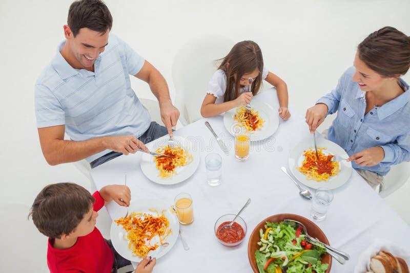 Panoramica di una famiglia che mangia pasta con salsa ed insalata fotografie stock libere da diritti