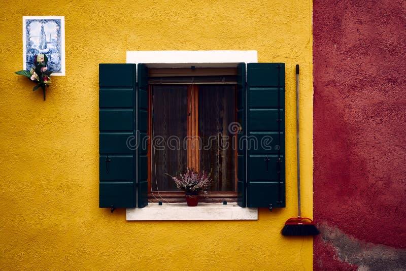Panoramica di una parete di costruzione gialla variopinta con una finestra e una pianta sul davanzale immagine stock libera da diritti