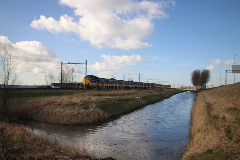Panoramica grandangolare di un treno interurbano del ICM del koploper sul fron L'aia della pista che si dirige al gouda fotografia stock