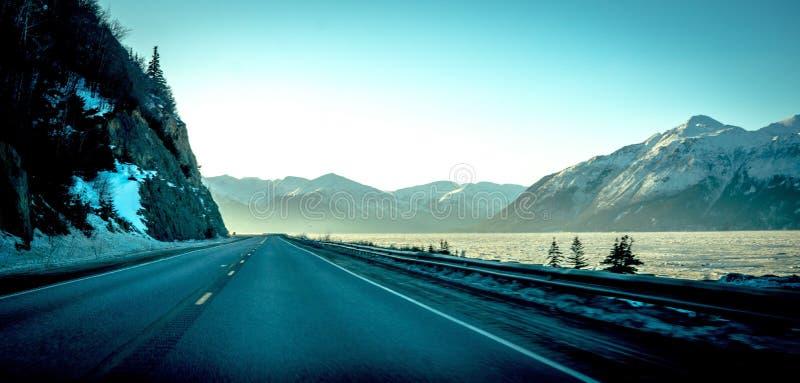 Panoramico ha sparato una strada stretta accanto ad un lago con lo stupore delle montagne rocciose alte coperte in neve immagini stock libere da diritti