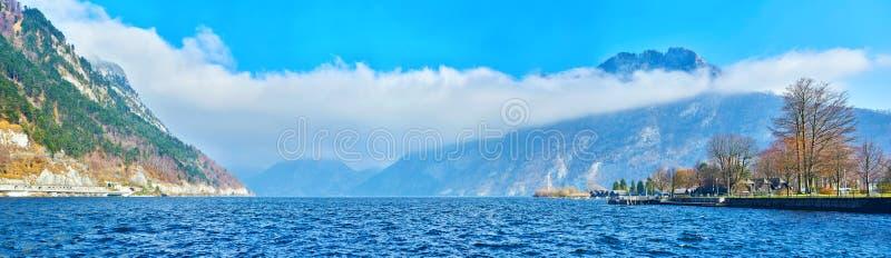 Panoramiczny foto halny jeziorny Traunsee z drzewami, domami i chmurami w Austria, Salzkammergut region fotografia royalty free