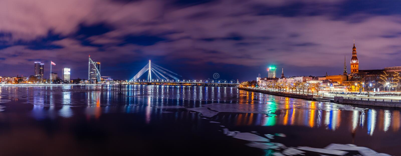 Panoramiczny pejzaż miejski Ryski, Latvia od Akmens mostu przy nocą z Dramatycznym niebem z widokiem budynki biurowi i inny, obrazy stock