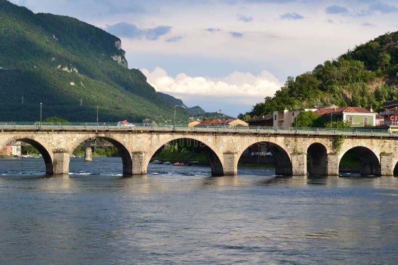 Panoramiczny widok antyczny łuku kamienia most nad Adda rzeką w Lecco w pogodnym wiosna dniu zdjęcia stock