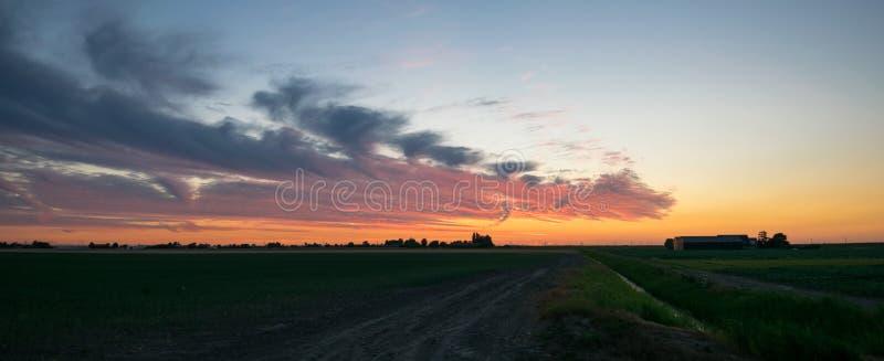 Panoramiczny widok głęboki - czerwony i purpurowy zmierzch nad gospodarstwem rolnym w holenderskiej wsi między, holandie zdjęcie stock