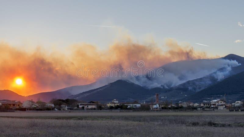 Panoramiczny widok położenia słońce na lasowym terenie palił wielkim spowodowany przez człowieka ogieniem, Monte Pisano, Tuscany, zdjęcie royalty free