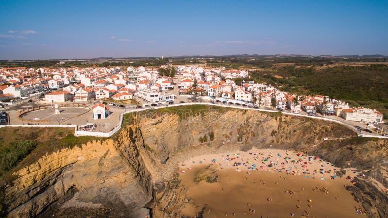 Panoramiczny widok Zambujeira De Mącący i plaża z wczasowiczkami zaludnia antenę zdjęcia stock