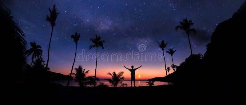 Panoramische Landschaft des Mannes stehend auf dem Kokosnussstrand mit Million Sternen und Sonnenaufgang lizenzfreies stockbild