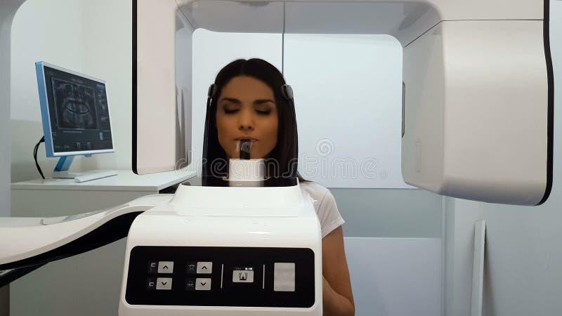 Panoramische x-ray machine in tandheelkundekliniek, vrouwelijke geduldige ondergaande procedure stock afbeelding