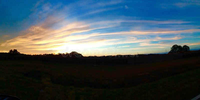 Panoramischer Himmel des Landsonnenuntergangs stockfoto