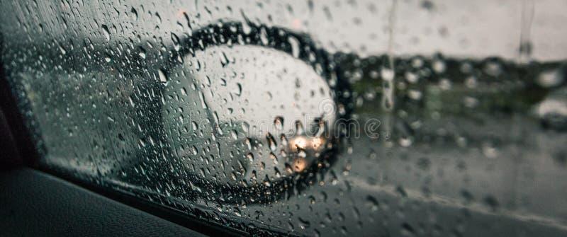 Panoramischer Schuss des Seitenspiegels eines Autos mit dem Fenster bedeckt in den Regentropfen stockbilder