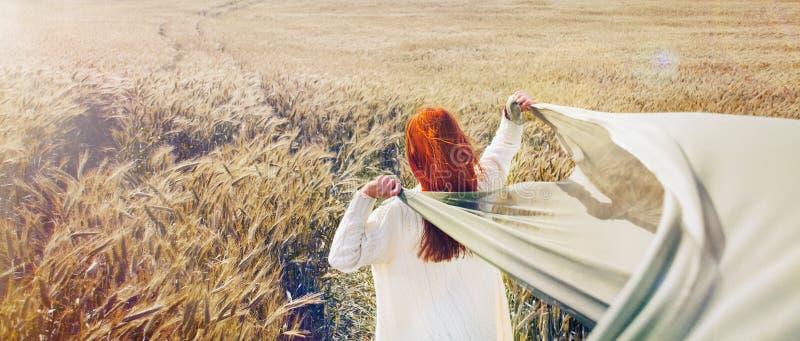 Panoramisches Bild der gehenden roten Haarfrau durch das einfache Feld lizenzfreie stockbilder