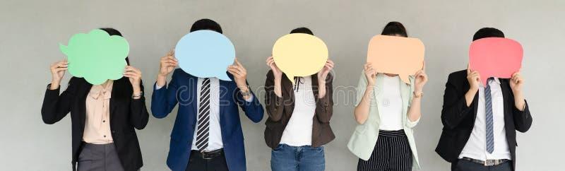 Panoramisches Fahnenbild von Geschäfts-Team Holding Speech Bubble-Ikone über grauem Hintergrund breite Ernte stockbilder