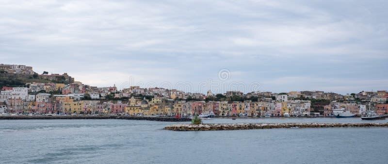 Panoramisches Foto der Hafenfront mit farbigen Pastellhäusern auf der Insel von Procida Italien, fotografiert vom Wasser stockfotografie