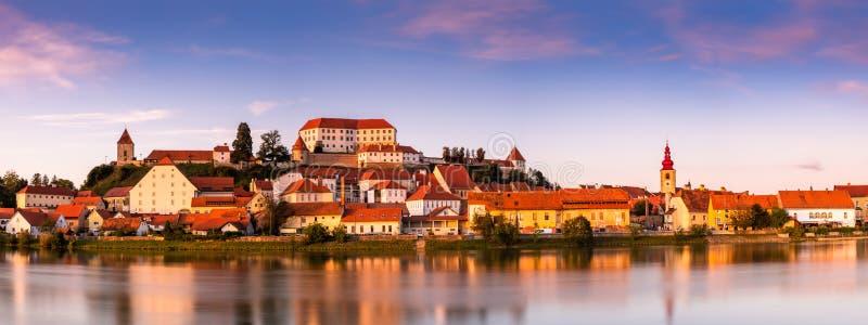 Panoramisk bild av Ptuj Cityscape i Slovenien Trädgårdsreflektion i floden Sunset arkivfoton