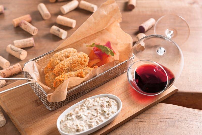 Panorera tungan av nötköttkalvköttet med yoghurtsallad och rött vin royaltyfri foto