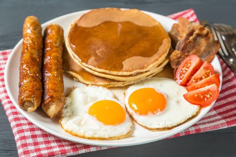 Panqueca com xarope do ovo, da salsicha, do bacon e de bordo fotografia de stock