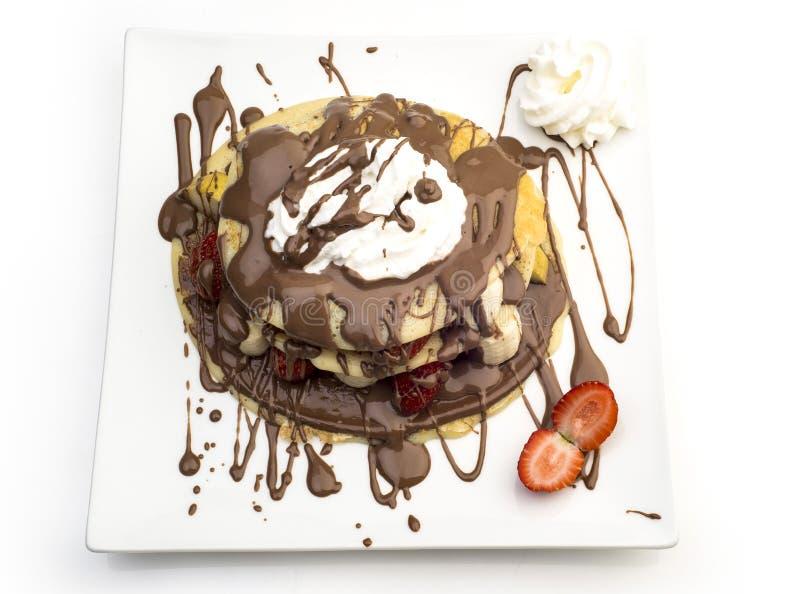 Panqueca do chocolate com as morangos, as bananas e o chantiliy isolados no branco imagens de stock royalty free