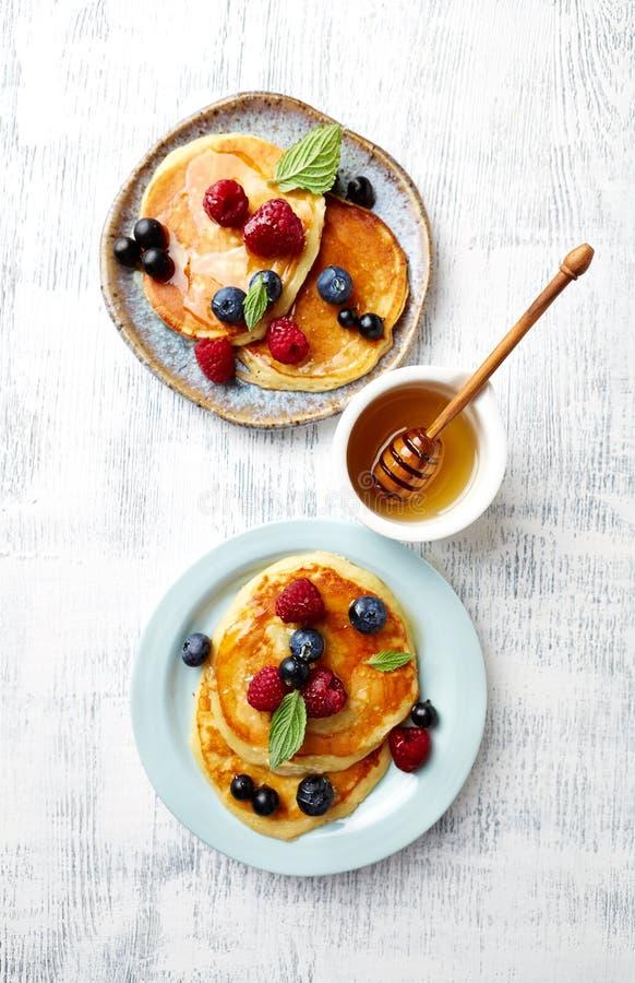Panquecas caseiros com frutos de baga, mel e folhas de hortelã fotografia de stock