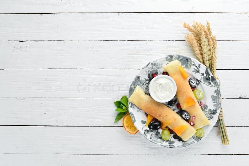 Panquecas com fruto e creme de leite Sobremesa fotografia de stock royalty free