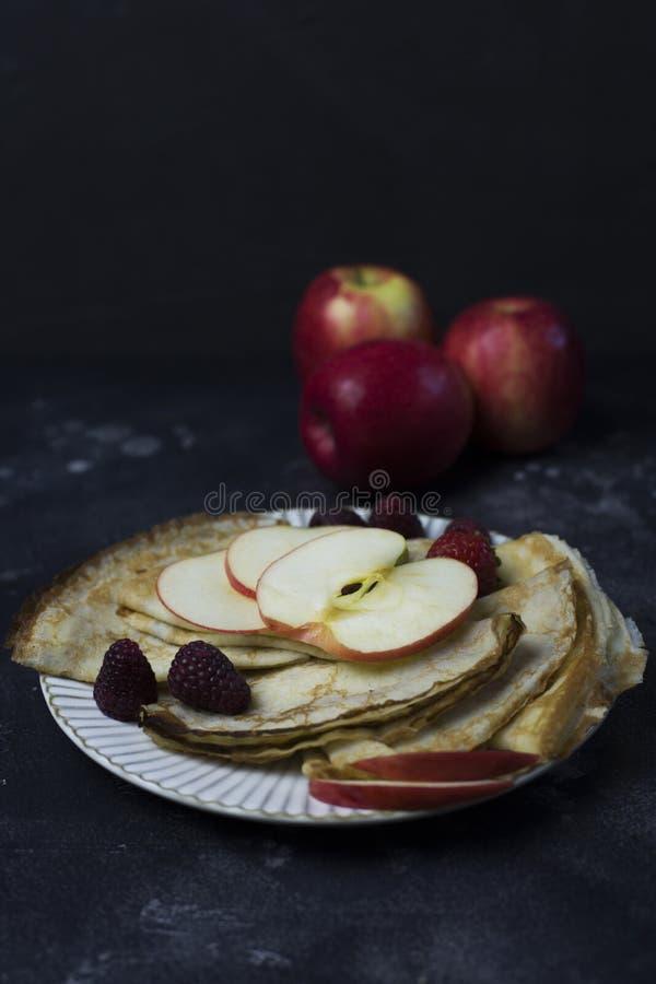 Panquecas com maçãs, framboesa e morango na placa branca no fundo preto foto de stock royalty free