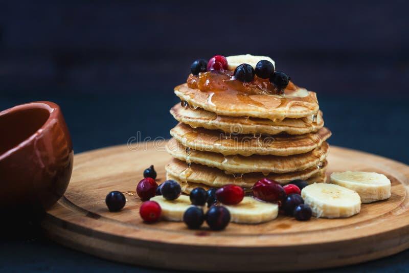 Panquecas com mel, bananas, doce e berrieson um menu de madeira da placa, conceito da receita do restaurante Servido dentro imagens de stock royalty free