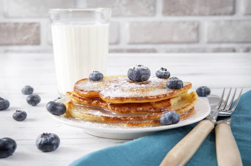 Panquecas com mirtilos em uma placa, um copo de leite, um garfo, uma faca em um guardanapo azul sobre um fundo branco de madeira imagens de stock