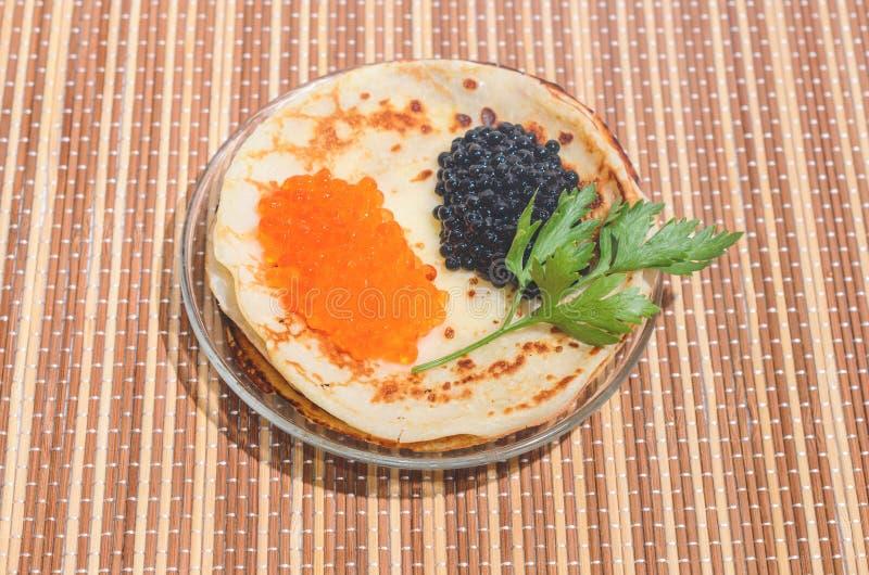 Panquecas com o caviar vermelho e preto e os verdes fotos de stock