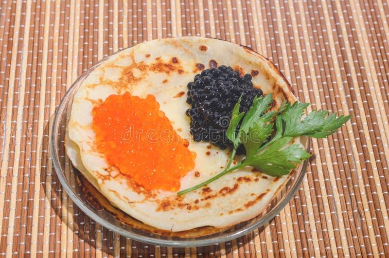 Panquecas com o caviar vermelho e preto e os verdes fotografia de stock