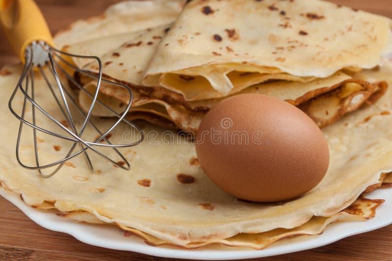 Panquecas com ovos e batedor de ovos na placa de corte de madeira fotografia de stock