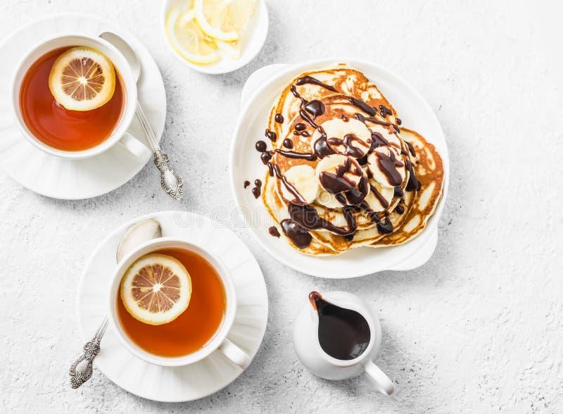Panquecas da farinha do coco com banana e molho e chá de chocolate com limão em um fundo claro, vista superior Café da manhã deli imagens de stock