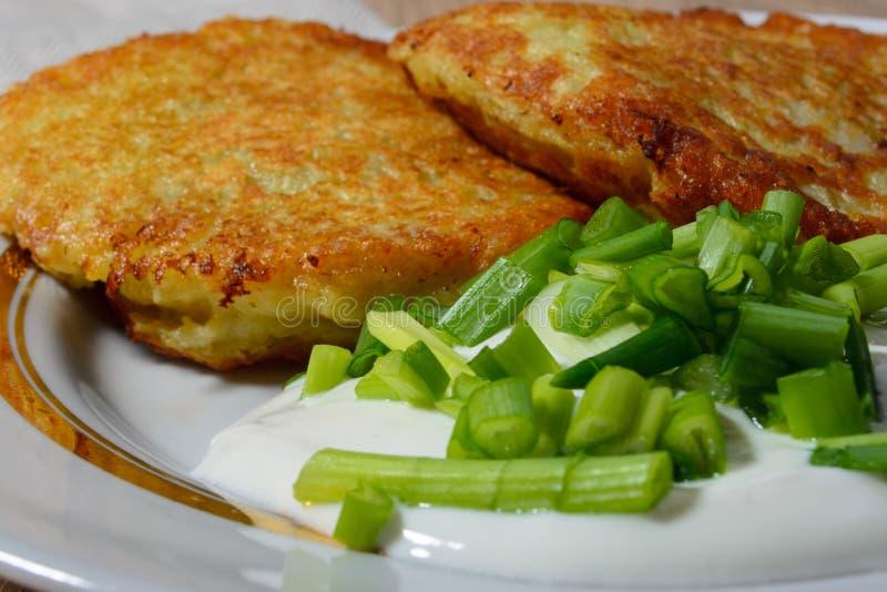 Panquecas de batata fritadas caseiros com creme de leite e as cebolas verdes foto de stock