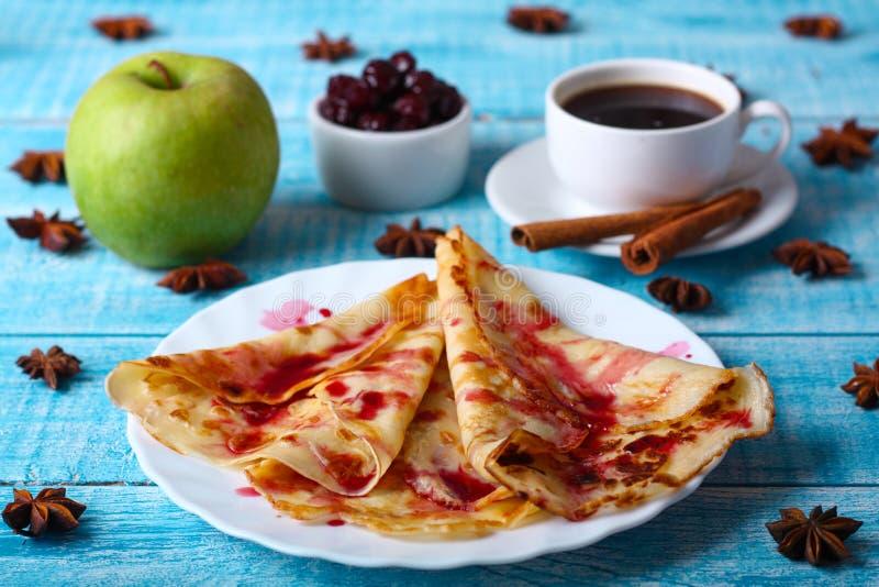 Panquecas do café da manhã com doce de cereja no fundo azul imagem de stock royalty free