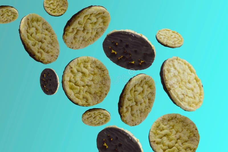 Panquecas do milho com o chocolate escuro que voa no ar em um fundo azul foto de stock royalty free