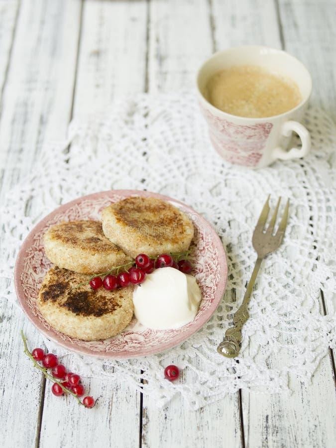 Panquecas do requeijão com bagas e creme de leite, copo do café preto, café da manhã saboroso imagem de stock