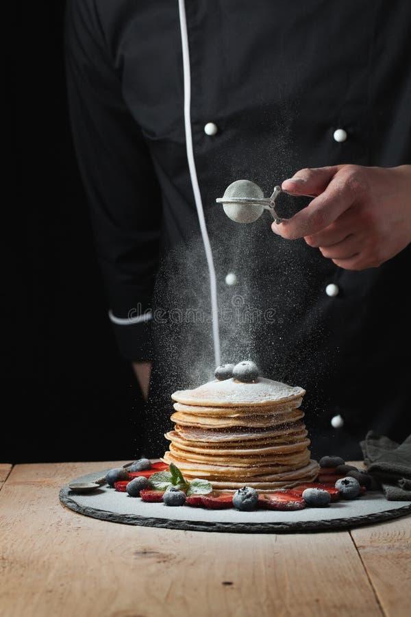 Panquecas do serviço com açúcar e as bagas pulverizados Mulher han do cozinheiro chefe imagem de stock