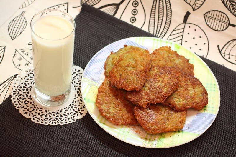 Panquecas e leite fritados de batata fotografia de stock royalty free