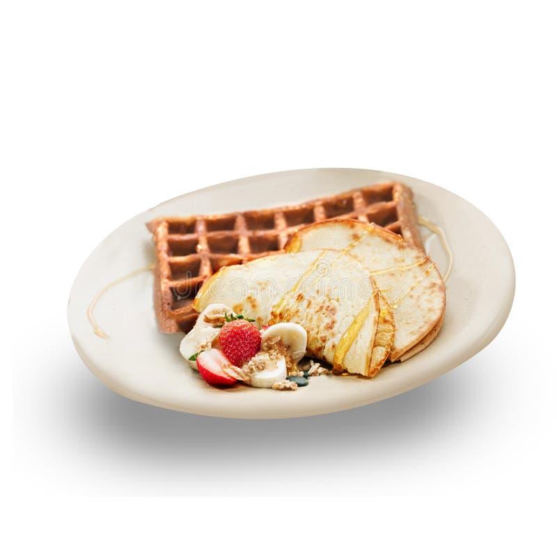 Panquecas e waffles, decorados com morangos, fatias da banana, e guarnição, derramada com mel Isolado em saudável e imagem de stock