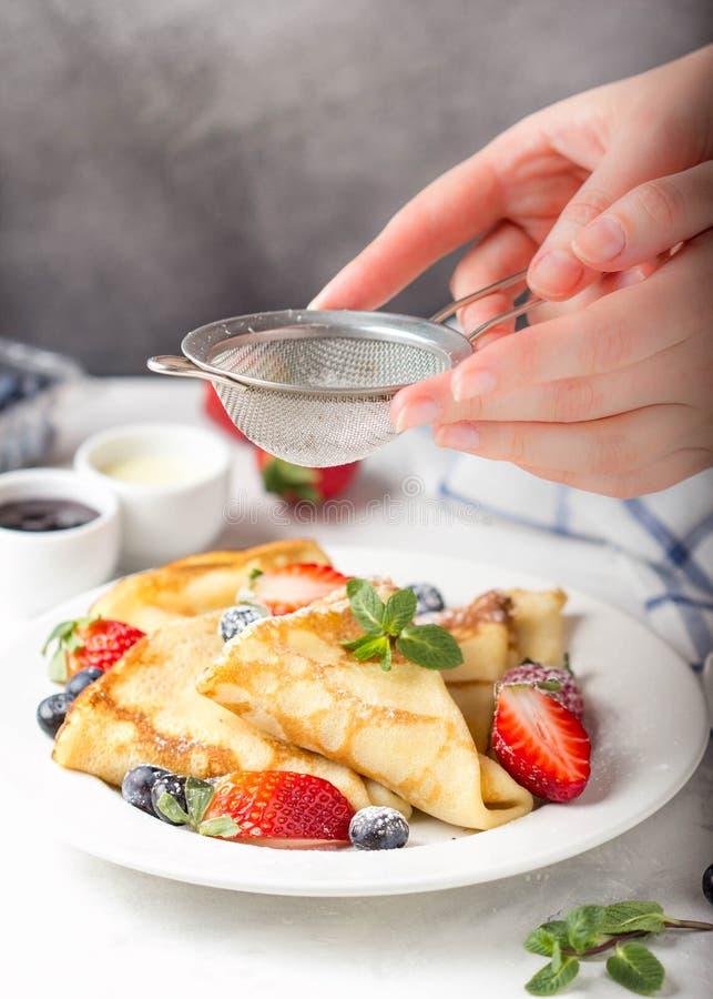 Panquecas finas com morangos e mirtilos, doce, leite condensado, sobremesa tradicional do russo delicioso do café da manhã para foto de stock royalty free