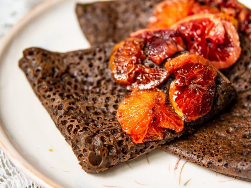 Panquecas finas do chocolate com molho das laranjas pigmentadas em uma placa branca no fundo cinzento com tela do laço Pilha de c imagens de stock