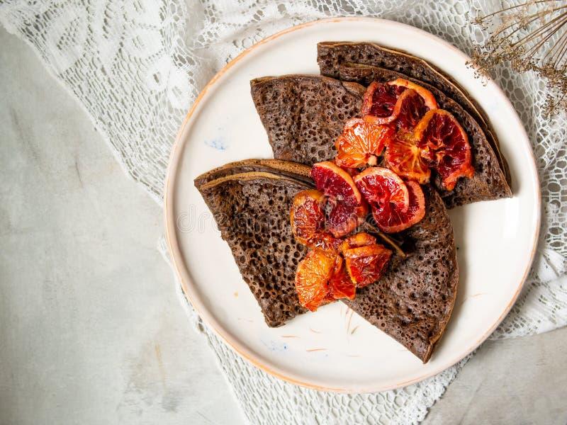 Panquecas finas do chocolate com molho das laranjas pigmentadas em uma placa branca no fundo cinzento com tela do laço Pilha de c imagem de stock