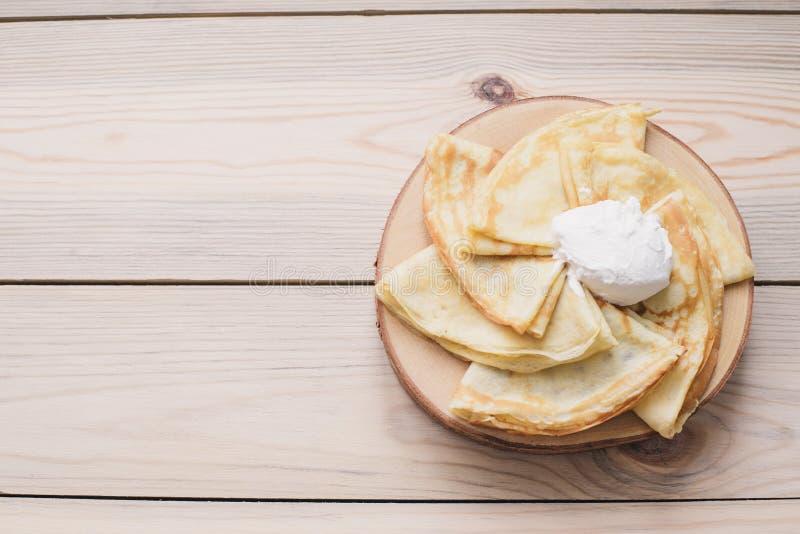 Panquecas finas do russo em um suporte de madeira feito da madeira natural com creme de leite Maslenitsa é um festival do aliment imagens de stock royalty free
