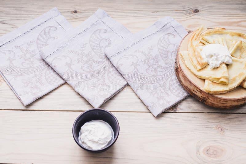Panquecas finas do russo em um suporte de madeira feito da madeira natural com creme de leite Maslenitsa é um festival do aliment imagem de stock