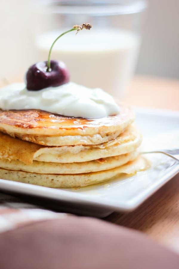 Panquecas inteiras do trigo do café da manhã com cereja e iogurte foto de stock
