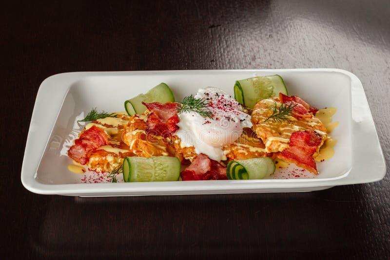 Panquecas, ovo escalfado e bacon do rosti da batata na parte superior imagem de stock royalty free