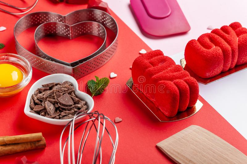 Pans hearts mold, whisk, eggs, wooden spatula and grated chocolate. Ingredients to making festive cake. Valentines Day bakeware stock photography