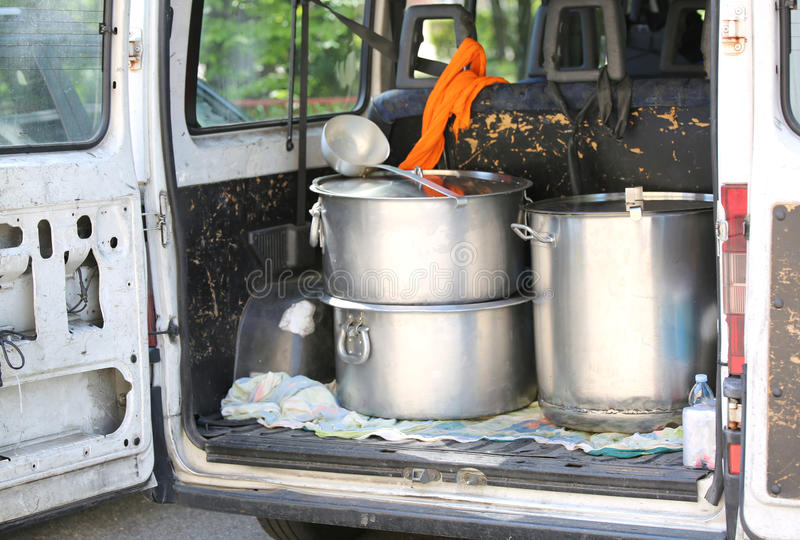 Pans for transporting food into the van trunk in a refugee camp. Pots for transporting food into the van trunk in a refugee camp for migrants royalty free stock image