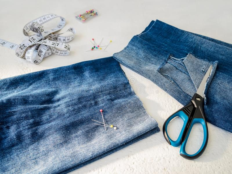 Pant leg with a large hole cut off with scissors from a blue jeans folded in a half. Making denim shorts. On a white. Background stock photos
