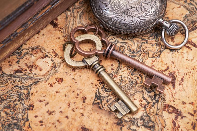 Panta rhei concept: Antique pocket watch, vintage keys and pile of old books on natural cork. Background stock photo