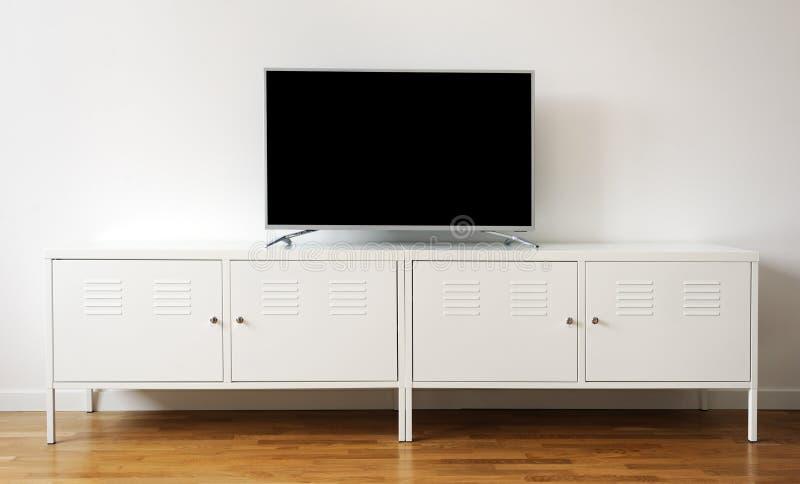 Pantalla ancha TV en el soporte blanco cerca de la pared ligera imagenes de archivo