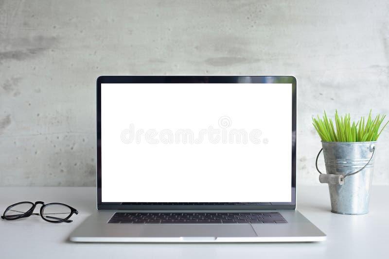 Pantalla blanca del ordenador portátil en vista delantera de la tabla del escritorio fotografía de archivo